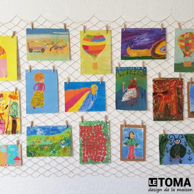 Kindermalereien am Dekonetz mit Klammern aufgehängt